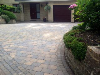 Block paving leading up to front door and garage of bath home