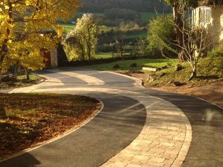 The block and tarmac driveway through the trees